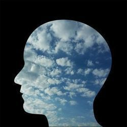 silhouette of a head superimposed over a photo of clouds