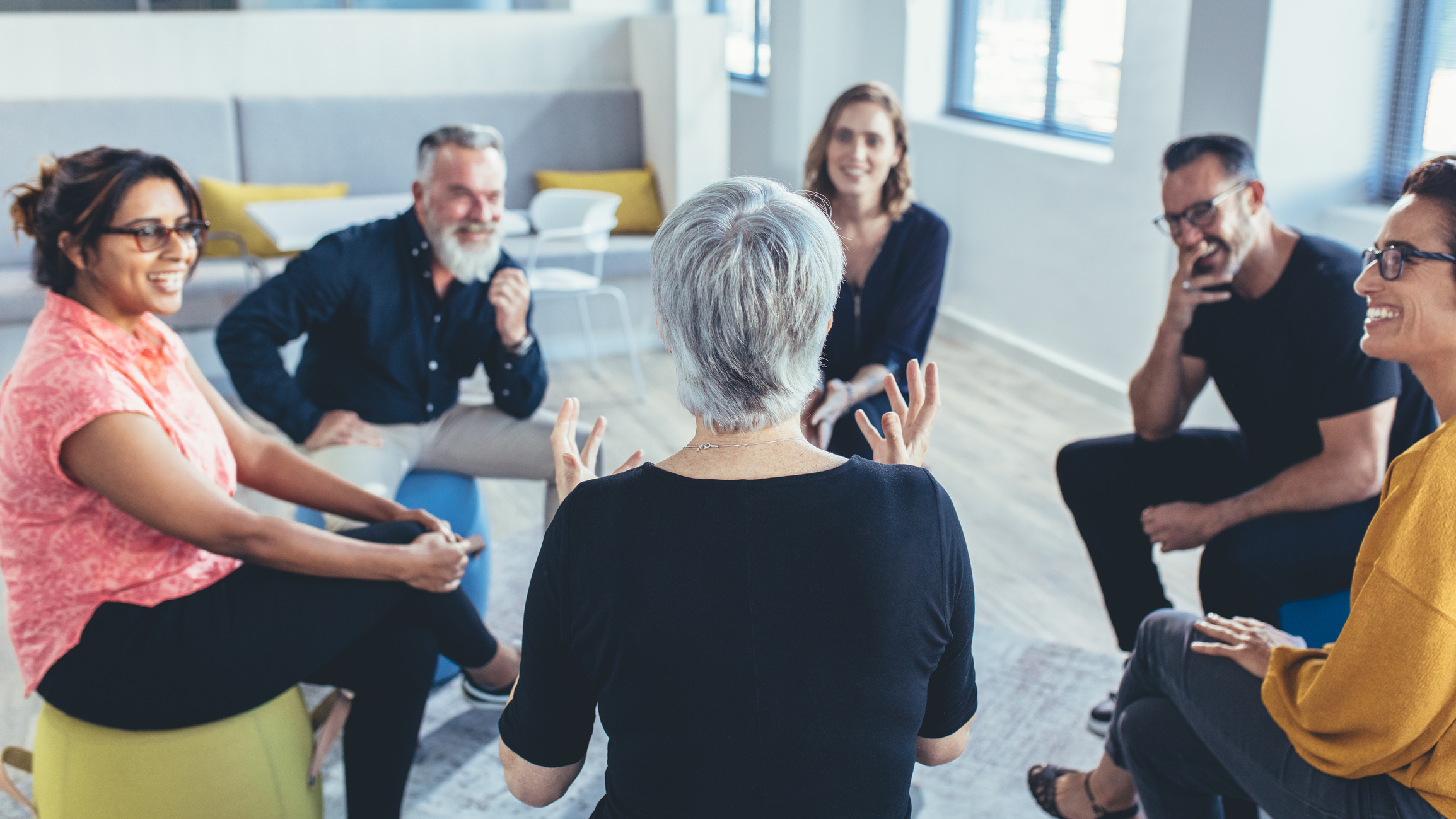 Group of business people sitting in circle and discussing in the office. Mature woman talking with coworkers in a team building session.
